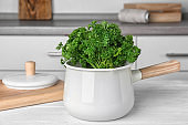 Saucepan with fresh green parsley on table