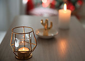 Burning candle in elegant holder on table