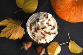 Flat lay composition with pumpkin spice latte in glass on dark background