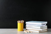Stack of hardcover books and color pencils on table against black background. Space for text