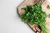 Wooden board with fresh green parsley and space for text on light fabric, top view