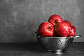 Juicy red apples in colander on table. Space for text