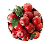 Juicy red apples in wicker basket on white background, top view