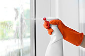 Cleaner washing window glass with detergent indoors, closeup