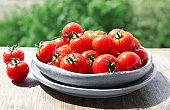 Plates with fresh ripe tomatoes on table outdoors