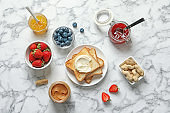 Flat lay composition with toast bread and toppings on marble background