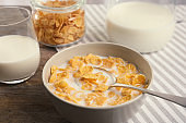 Healthy cornflakes with milk in bowl served on table