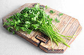 Wooden board with fresh green parsley on light fabric