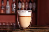 Glass with delicious latte on counter in bar