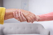 People holding hands together indoors. Help and elderly care service