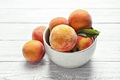 Bowl with delicious ripe peaches on wooden background