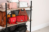 Shelving unit with stylish purses near white wall, space for text. Element of dressing room interior