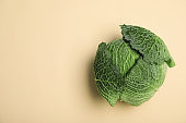 Fresh green savoy cabbage and space for text on color background, top view