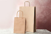 Mockup of paper shopping bags on table against color background