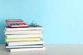 Stack of hardcover books and calculator on table against color background, space for text