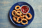 Plate with homemade crunchy fried onion rings and tomato sauce on wooden background, top view