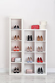 Wardrobe shelves with different stylish shoes indoors. Idea for interior design