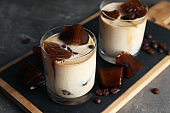 Glasses of milk with coffee ice cubes on grey table