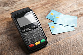 Modern payment terminal and credit cards on wooden background