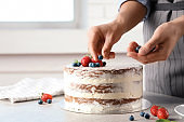 Woman decorating delicious cake with fresh berries at table. Homemade pastry