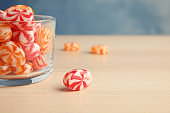 Glass with delicious colorful candies on wooden table. Space for text
