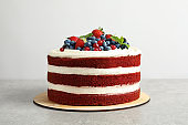 Delicious homemade red velvet cake with fresh berries on white background