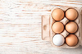 Carton of raw chicken eggs on wooden background, top view. Space for text