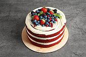 Delicious homemade red velvet cake with fresh berries on table