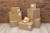 Stacked parcel boxes on floor against brick wall