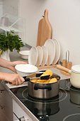 Woman preparing corn in stewpot on stove, closeup