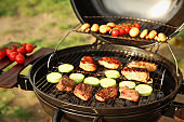 Modern grill with meat and vegetables outdoors, closeup. Camping cookout