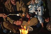 Friends frying marshmallows on bonfire at night, closeup. Camping season