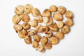 Heart shaped heap of dried figs on white background, top view. Healthy fruit