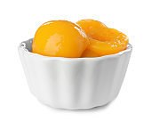 Bowl with halves of canned peaches on white background