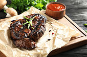 Delicious barbecued steak served with sauce on wooden board