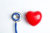 Stethoscope and heart model on light background, top view. Medical equipment