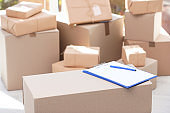 Clipboard, cardboard box and blurred stacked parcels on background, indoors