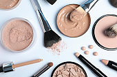 Flat lay composition with skin foundation, powder and beauty accessories on white background