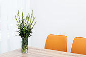 Beautiful bouquet in vase on wooden table against color background. Stylish interior