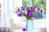 Beautiful bouquet of purple eustoma flowers in vase on table