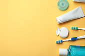 Flat lay composition with toothpaste, oral hygiene products and space for text on color background