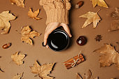 Woman in autumn sweater holding cup of hot cozy drink on color background, top view