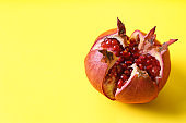 Ripe pomegranate on color background, space for text