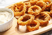 Homemade crunchy fried onion rings and sauce on wooden dish, closeup