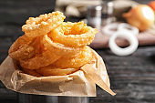 Dishware with homemade crunchy fried onion rings on wooden table, closeup