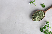 Spoon with dry parsley and space for text on grey background, top view