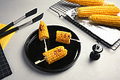 Ceramic plate with grilled corn cobs on light background