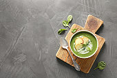 Fresh vegetable detox soup made of spinach with croutons in dish served on table. Space for text