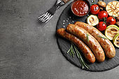 Flat lay composition with delicious barbecued sausages and vegetables on gray background. Space for text