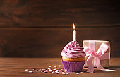 Gift box and delicious birthday cupcake with candle on table
